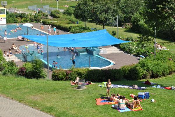 Ein Sonnensegel wird in einem Freibad als Schattenspender genutzt.