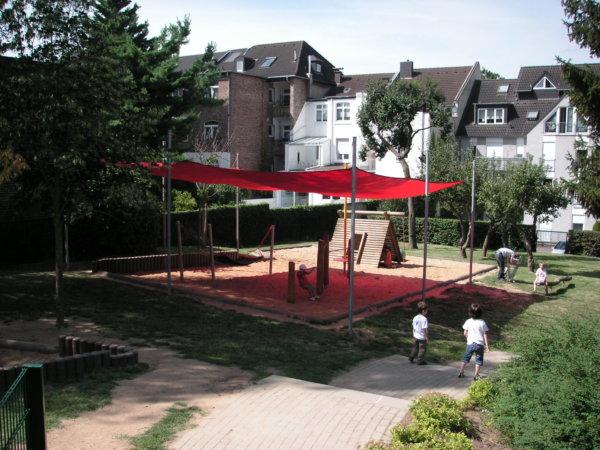 Ein rotes Sonnensegel beschattet Spielgeräte auf einem Spielplatz.