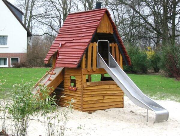 Eine Spielhütte aus Holz mit Kletter- und Rutschelement