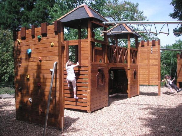 Ein Kind klettert eine Holz-Burg auf einem Spielplatz hoch.