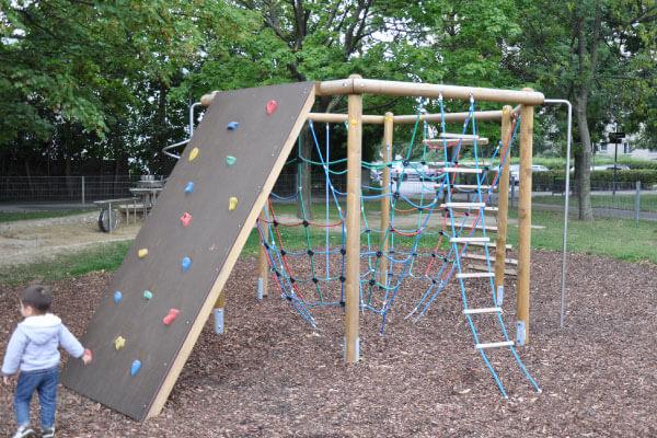 Ein Spielgerät mit Kletterwand und Kletternetzen steht auf einem Spielplatz.