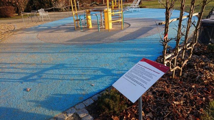 Ein Schild weißt die blaue Spielfläche und das Karussell als inklusiv aus.