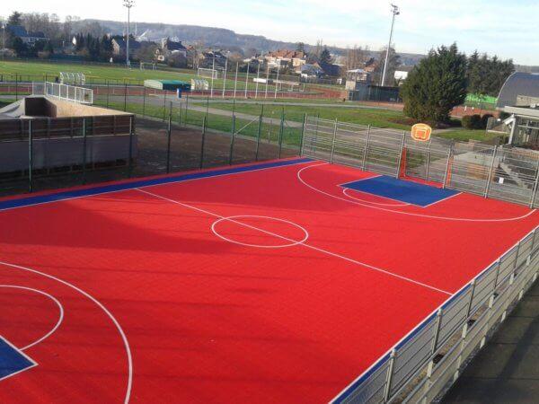 Eine rot-blaue Multisportanlagen, die Sportgeräte für Basketball und Fußball vereint.