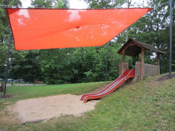 Ein roter Sonnenschutz über einem Spielplatz