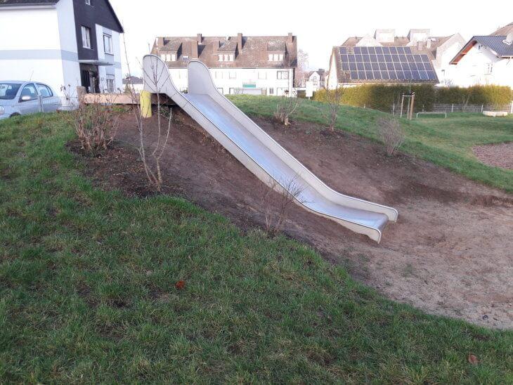 Der Hang neben einer Rutschbahn ist vom Spielen abgetragen.