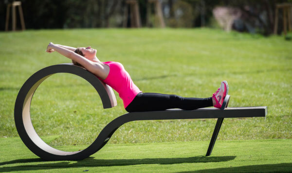 Eine junge Frau dehnt ihren Rücken auf einem Outdoor-Fitnessgerät.