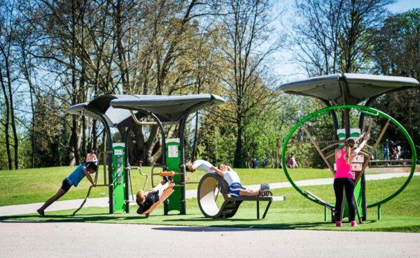 Mehrere Menschen trainieren an einer großen Outdoor-Fitnessanlage.