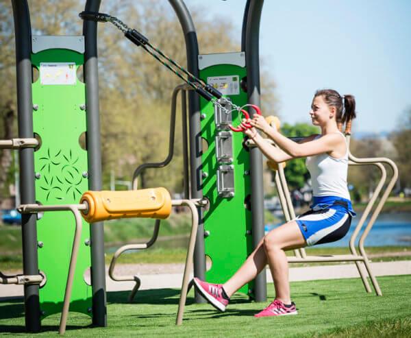 Eine junge Frau macht ihr Calisthenics-Workout an Sportgeräten von Husson.
