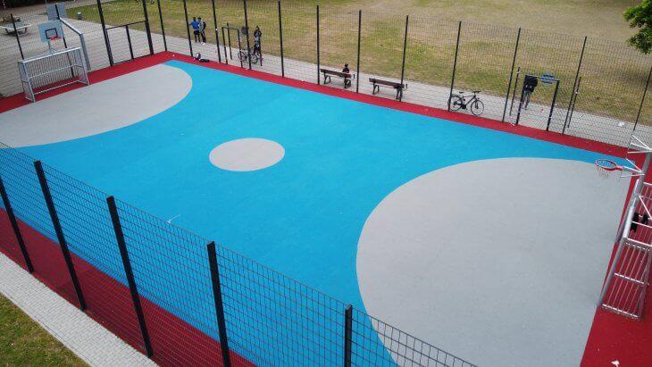 Eine Multisportanlage mit blau-weiß-rotem Teppichvlies