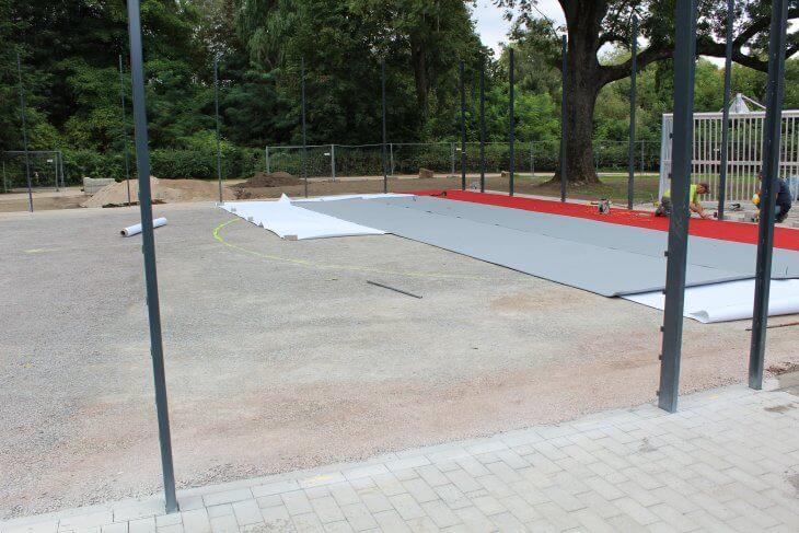 Ein Bolzplatz während der Entstehungsphase: Das Bild zeigt, wie das Teppichvlies verlegt wird.